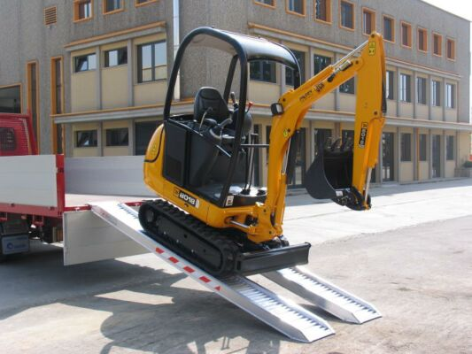 Mini digger unloading from truck