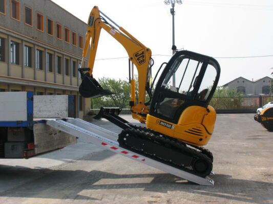 Mini digger loading on to tipper truck