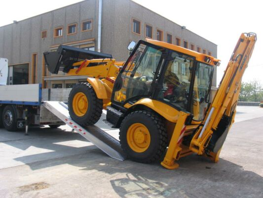 Digger driving on to loading ramps