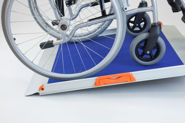 Wheelchair on premium non-folding wheelchair ramp with blue grip surface
